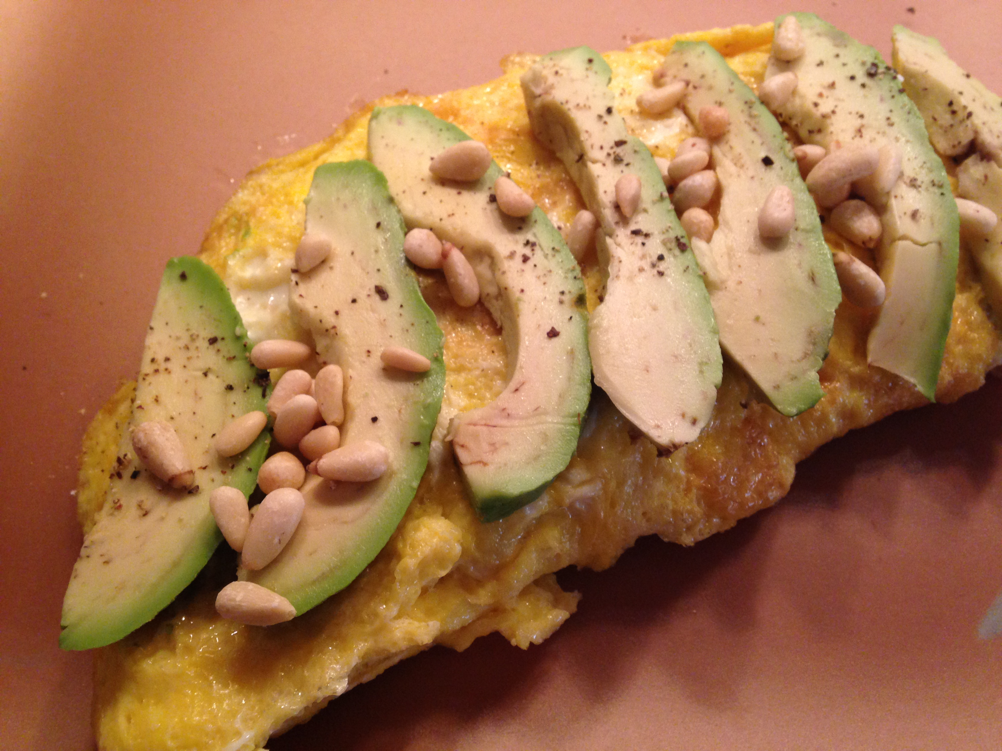 Healthy breakfast omelet with fresh spinach, feta, avocado and pine nuts.